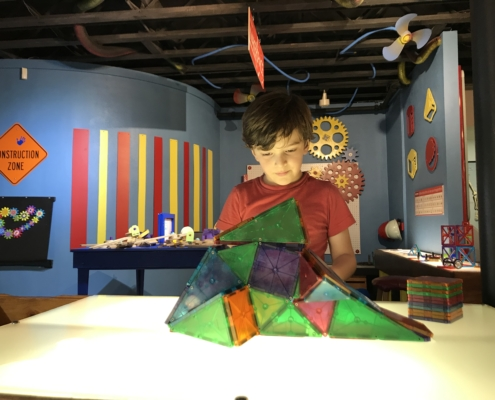 child exploring hands on learning exhibit at children's museum